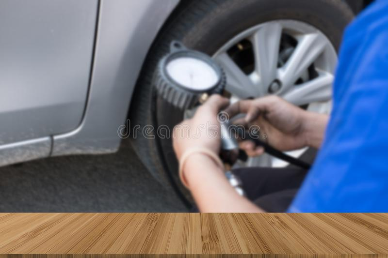 Tire Inflator. mechanic holding gauge for car tyre pressure meas. Urement. hand inflating auto wheel with wood table for display your product royalty free stock image