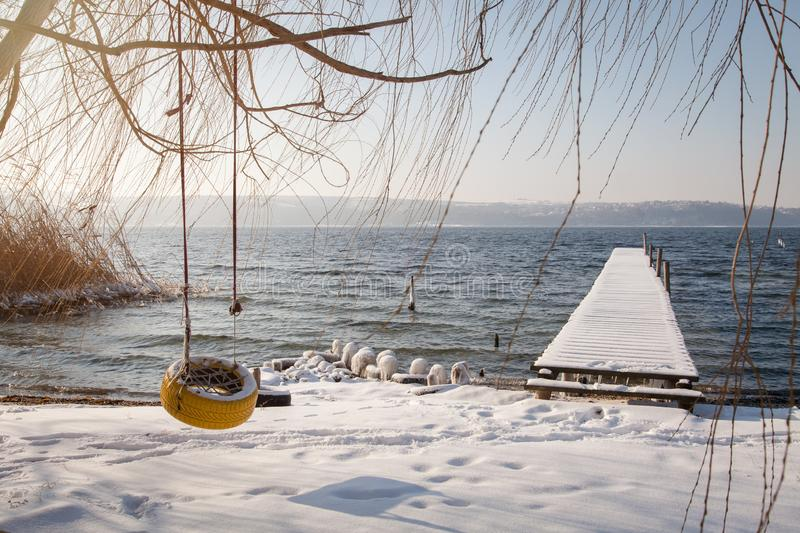 Tire swing on tree at the lake in winter, near old fishing bridge. Tire swing on tree at the lake in winter, near fishing bridge stock images