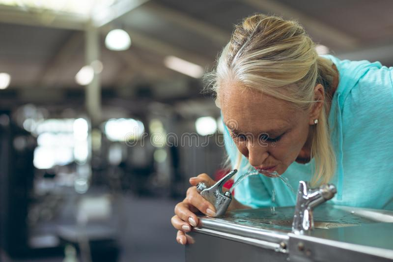 Tired active senior woman drinking tap water in fitness center stock photography