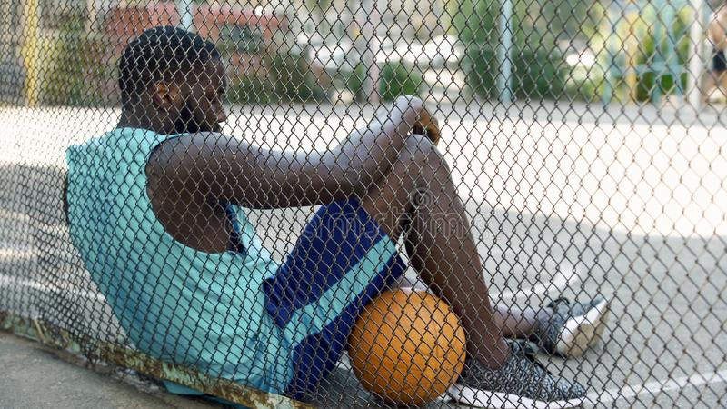 Tired African-American basketball player relaxing after game at stadium, hobby royalty free stock photos