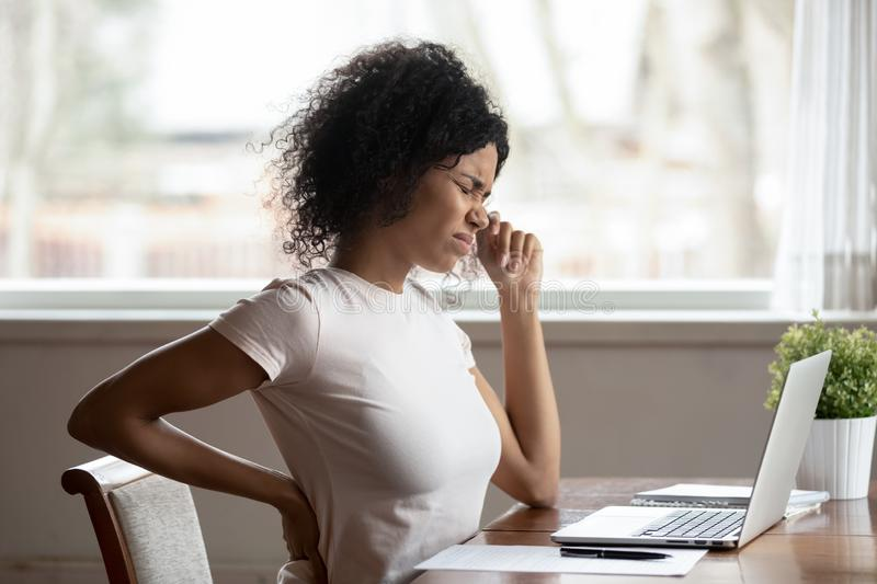 Hurt biracial woman work at laptop suffer from spinal spasm. Tired african American millennial female worker sit at desk touch back suffer from lower spinal stock photos