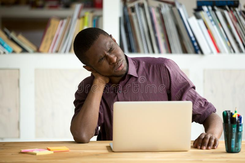 Tired African American office worker suffering from neck pain stock photos