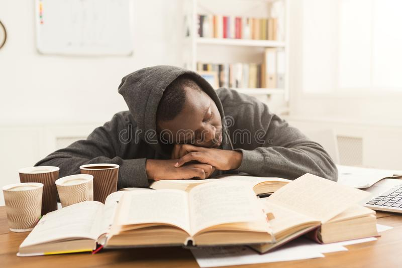 Black male student studying at table full of books royalty free stock photos