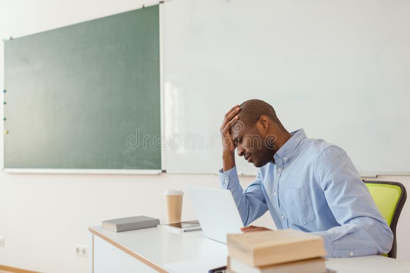 Tired african american teacher sitting at table with laptop and coffee cup stock image