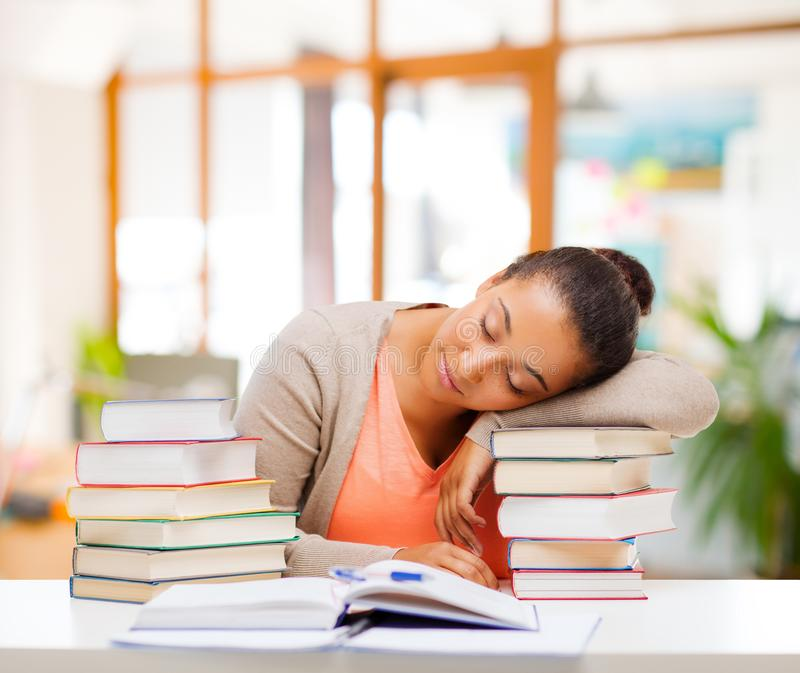 Tired african female student sleeping on books royalty free stock photo