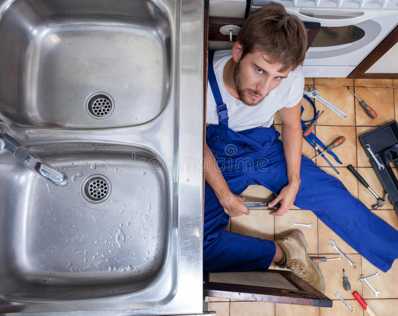 Tired and annoyed handyman. During repair sink royalty free stock photo