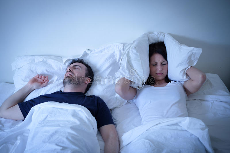 Tired and annoyed woman of her boyfriend snoring in bed stock images
