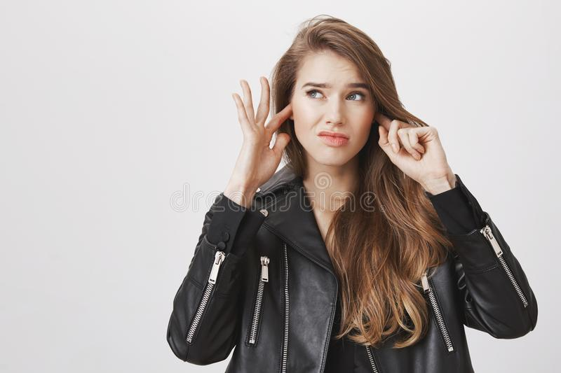 Tired of annoying noises outside. Charming urban woman in leather jacket covering ears and feeling irritation from loud stock photography
