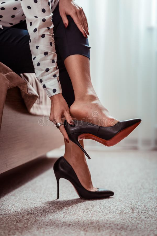 Free Tired Appealing Lady Taking Off Black High Heels After Long Working Day Royalty Free Stock Images - 152970279