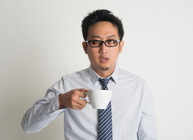 Tired Asian businessman drink coffee. Tired Asian businessman with dark eyes circle holding coffee cup on plain background stock photography