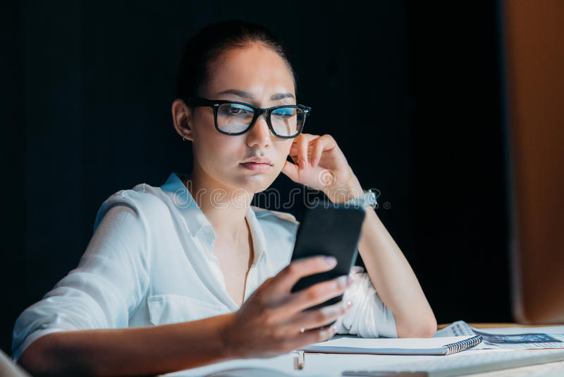 Tired asian businesswoman in eyeglasses using smartphone and working till late in office. Young tired asian businesswoman in eyeglasses using smartphone and stock photos
