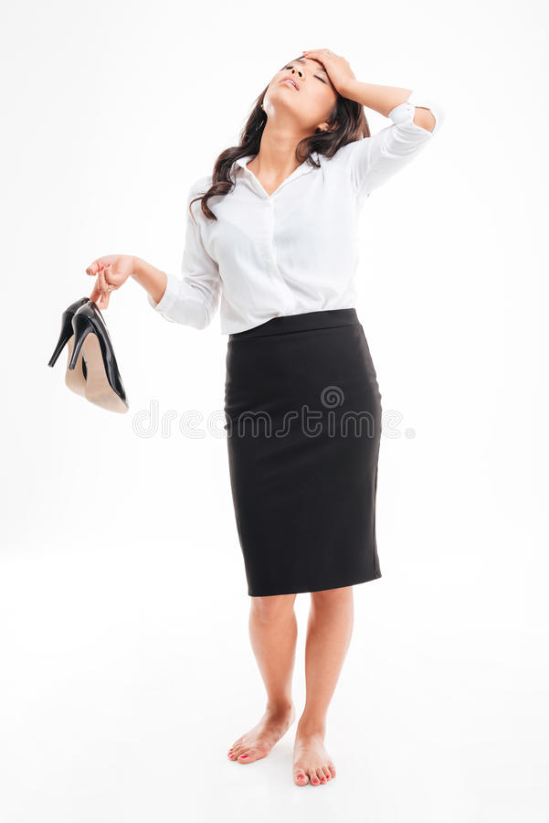 Tired asian businesswoman standing barefoot and holding high heels shoes. Tired exhausted young asian businesswoman standing barefoot and holding high heels royalty free stock image