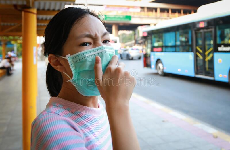 Tired asian child girl cough wearing hygienic mask,stressed worried about air pollution problems,toxic fumes,PM 2.5,dust,bad. Environment at bus stop in city stock images