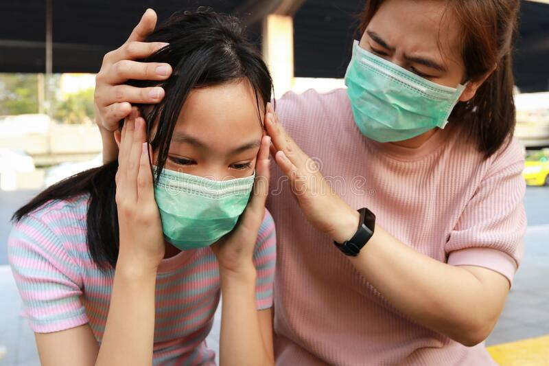 Tired asian child girl crying with hygienic mask suffer from headache and air pollution,allergy to dust,feel sick,dizzy,people. Wearing face mask protection royalty free stock photos