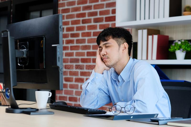 Tired asian man sleeping at office desk. Young businessman with eyeglasses overworked and fell asleep, Creative casual man. Sleeping at his working place stock photo