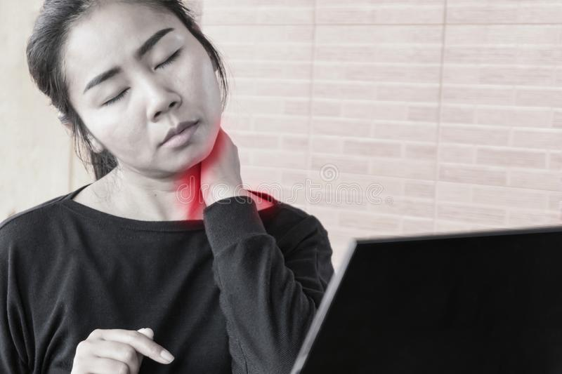 Tired Asian woman having neck pain while working on computer laptop royalty free stock images
