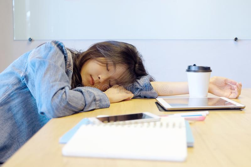 Tired asian woman sleeping at office desk. Young asian woman university student fell asleep in classroom, Creative casual woman royalty free stock image