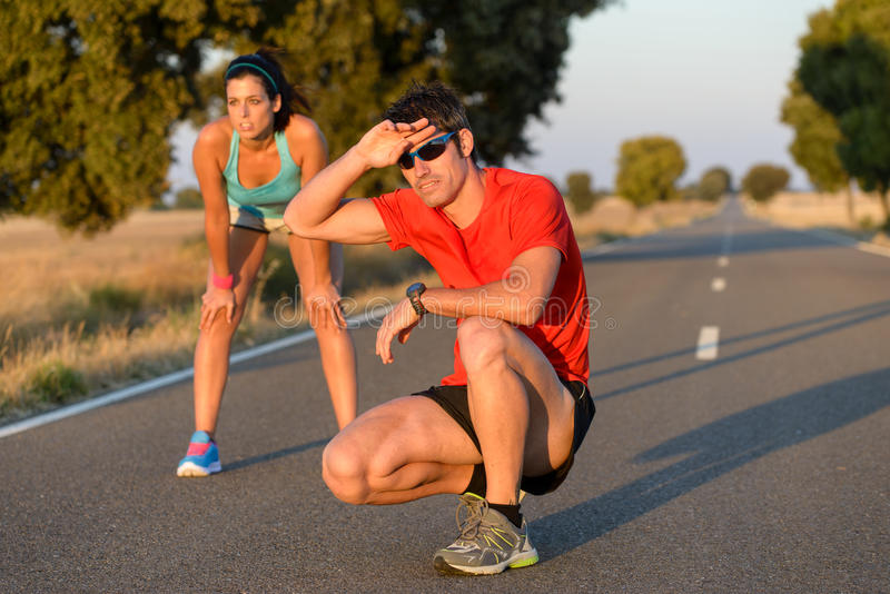 Tired athletes after running in road. Tired fitness couple of runners sweating and taking a rest during marathon training in country road. Sweaty athletes after royalty free stock photography