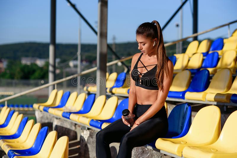 Tired attractive girl sitts on the stadium tribune after training. Sport, health care concept. stock photography