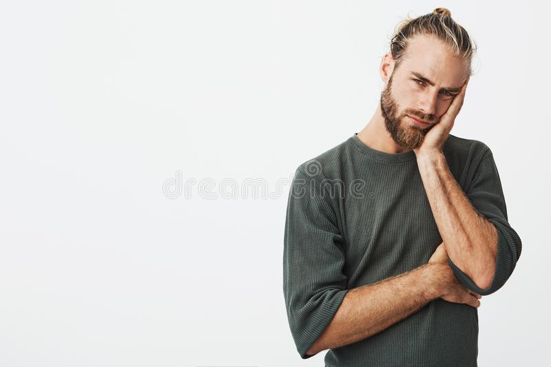 Tired attractive man with stylish hairstyle and beard in grey shirt exhausted looking at camera with exhausted stock images