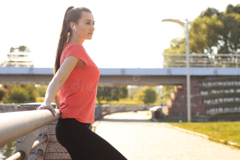 Tired attractive young woman in sports clothing relaxing while standing outdoors stock photo