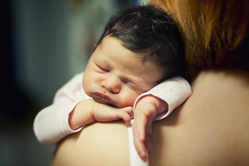 Tired baby sleeping. Cute tired baby sleeping on mother's shoulder royalty free stock image