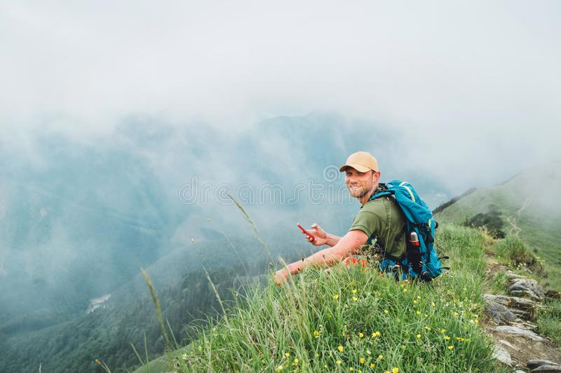Tired backpacker man browsing internet using smartphone enjoying cloudy valley bottom walking by the foggy cloudy weather mountain royalty free stock photos