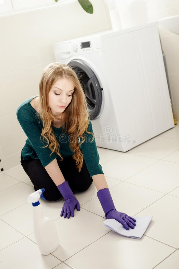 Tired beautiful blond woman washes the floor stock photography