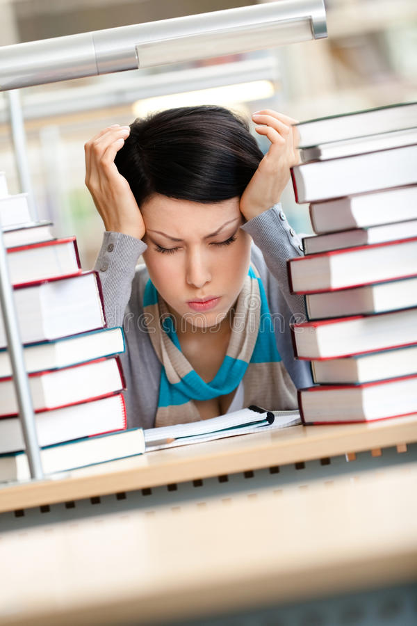 Tired beautiful woman surrounded with books royalty free stock photos