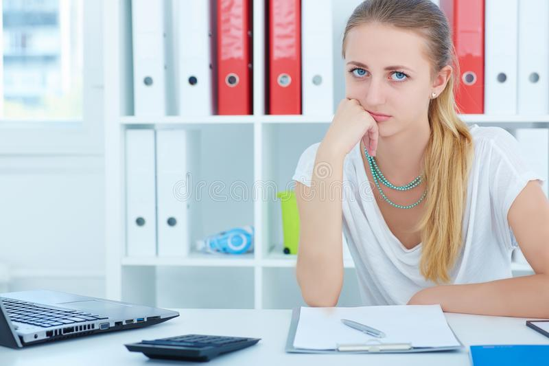 Young beautiful tired girl sits propped head in his hands at a desk in the office and looking at the camera. royalty free stock image