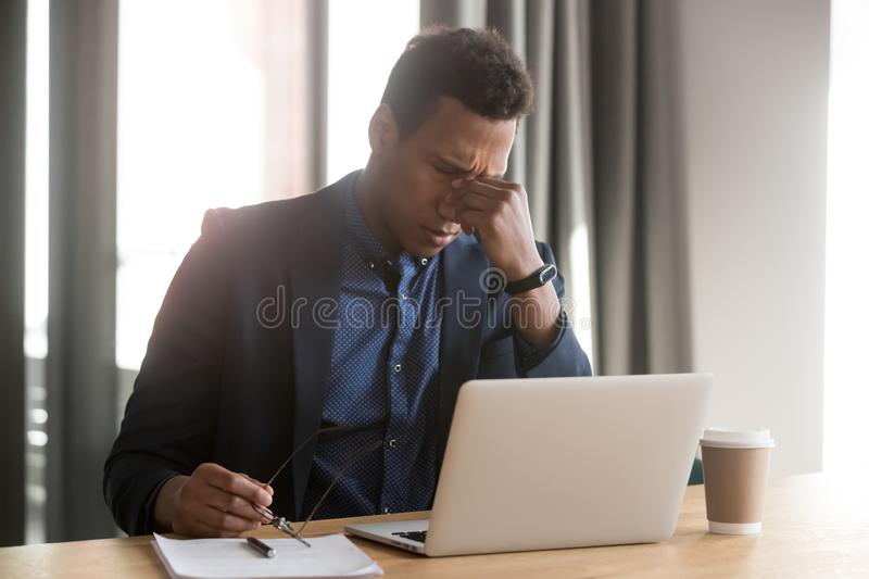 Tired black businessman take off glasses suffering from headache. Tired african American businessman use laptop take off glasses suffering from blurry vision royalty free stock photography