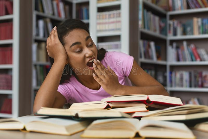 Tired afro girl yawning while reading books in library stock photos