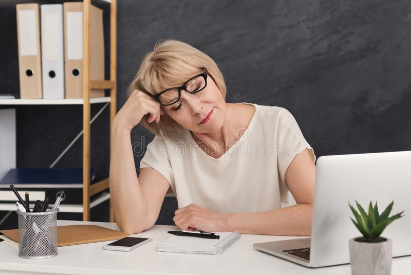 Tired blonde business woman sitting with closed eyes royalty free stock photo
