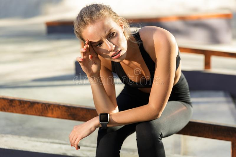 Tired bored oung sports woman sitting outdoors looking aside. stock photography