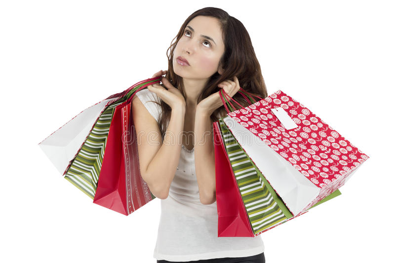 Tired and bored shopping woman. Woman looking tired and bored, holding the paper shopping bags, isolated on white background stock photo