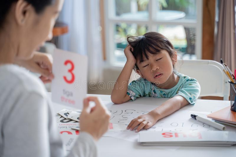 Tired and bored toddler while studying with mother royalty free stock photography