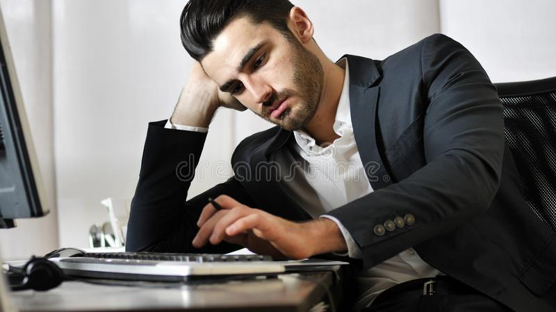 Tired bored young businessman in office royalty free stock photos