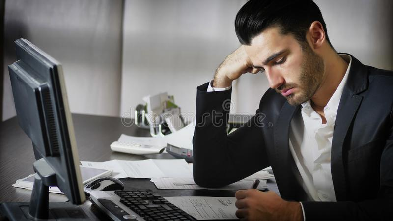 Tired bored young businessman in office royalty free stock photography
