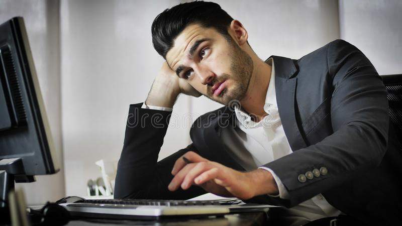 Tired bored young businessman in office stock image