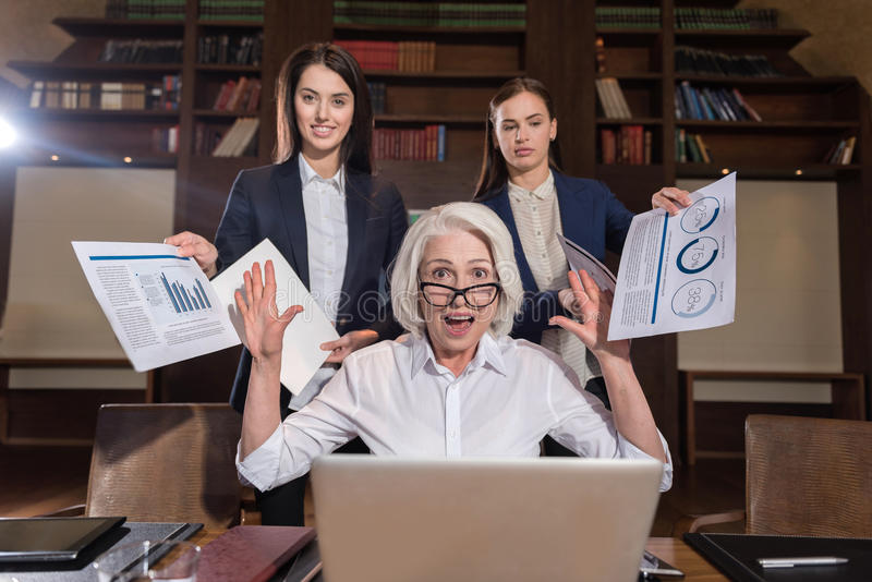 Tired boss and her female colleagues posing in office royalty free stock photo