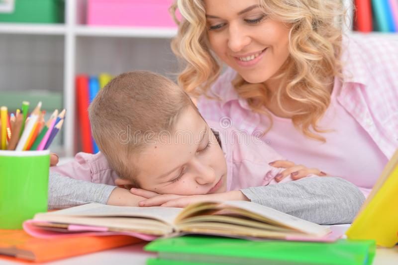 Tired boy sleeping on books at home stock photo