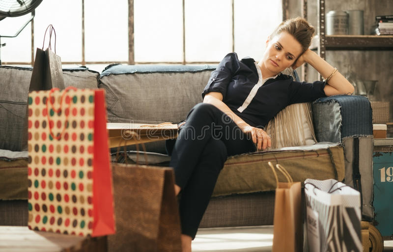Tired brunet woman sitting on couch among shopping bags in loft. Shopping relieving stress? Tired frustrated brunette woman in elegant clothing sitting on couch royalty free stock photo