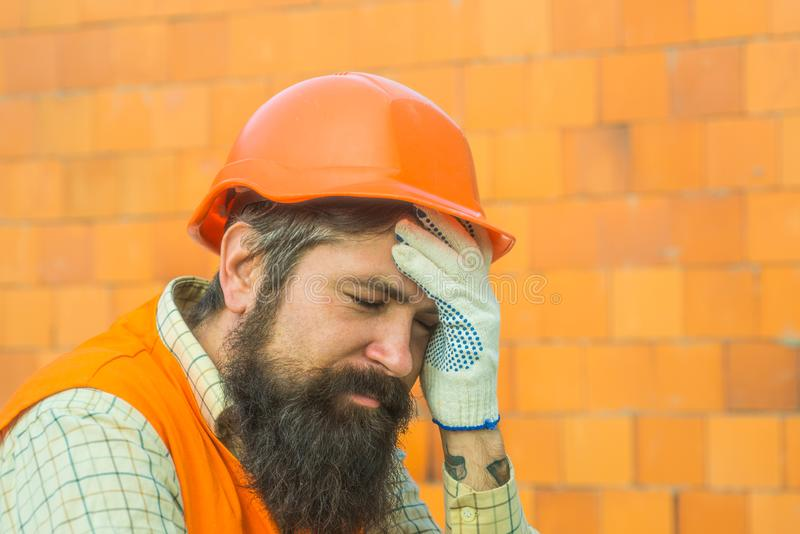 Tired builder. Construction site. Hard work. Earnings abroad. Fatigue. The builder has a headache. Production noise. Tired builder. Construction site. Hard work stock photography