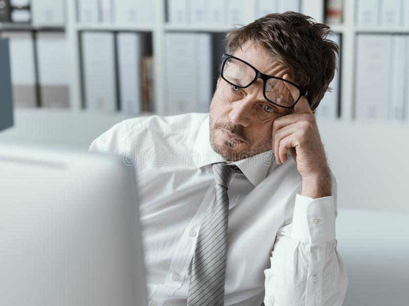 Tired business executive working with his computer royalty free stock photos
