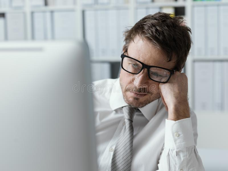 Tired business executive working with his computer stock photography