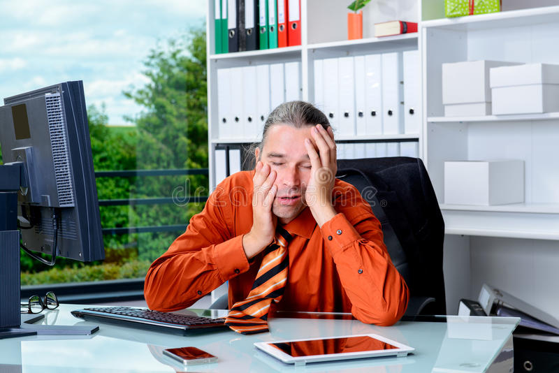 Tired business man lying with head in hands is over-worked. Young tired business man lying with head in hands is over-worked stock images