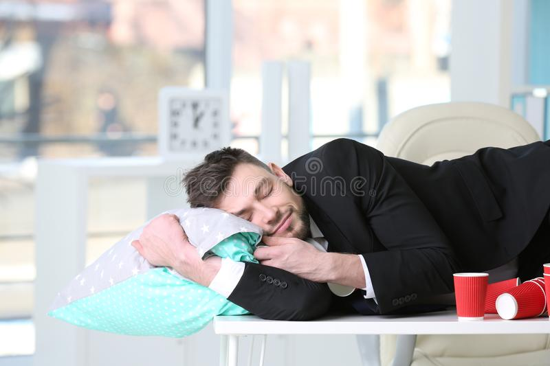 Tired business man sleeping among empty paper coffee cups stock photo
