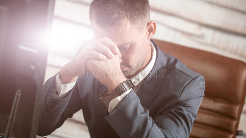 Tired business man at workplace in office holding his head on hands. Sleepy worker early in the morning after late night work. Ove. Tired business man at stock photography