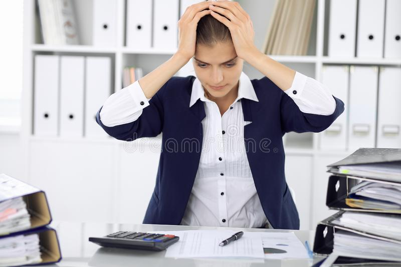 Tired business woman or female accountant with bills and paper folders in office stock photography