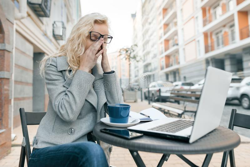 Tired business woman with laptop in outdoor cafe, woman touching her eyes with her glasses off, city street background stock photos